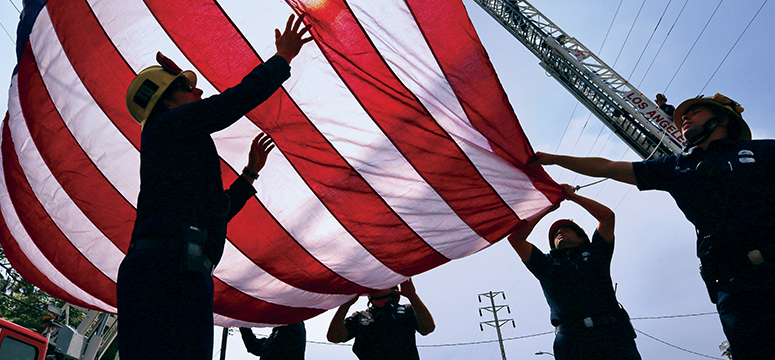 Firefighters working together to raise an American flag