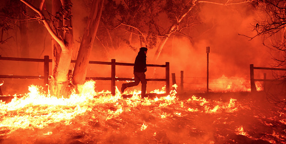 Wildland firefighter runs across a yard filled with flames