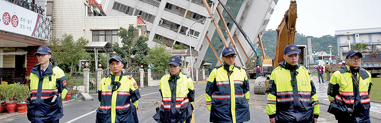 Taiwanese Police block off a toppled building