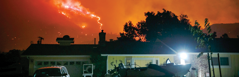 Home with a raging wildfire in the background