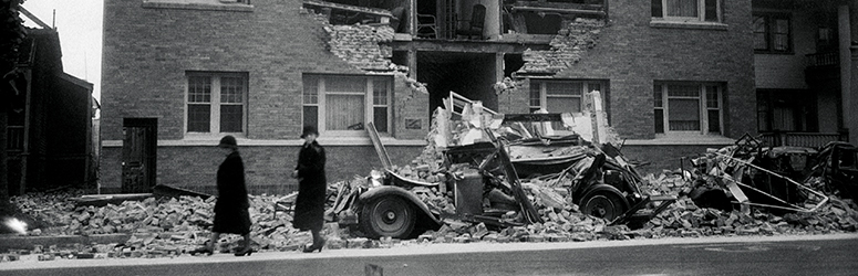 Two women walk past rubble of a building after the LA earthquake of 1933