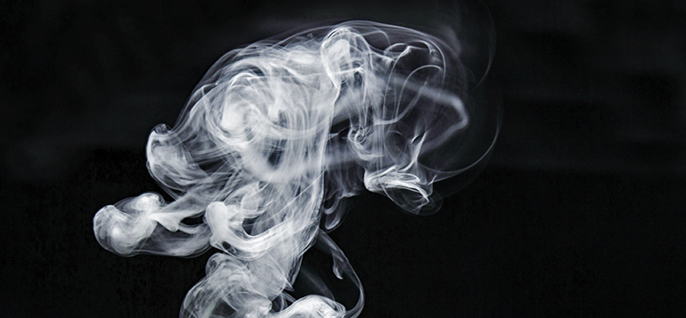 Smoke wafts through a black background