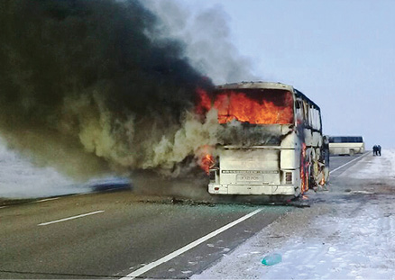Bus fully engulfed in flames on the side of a highway in Kazahstan