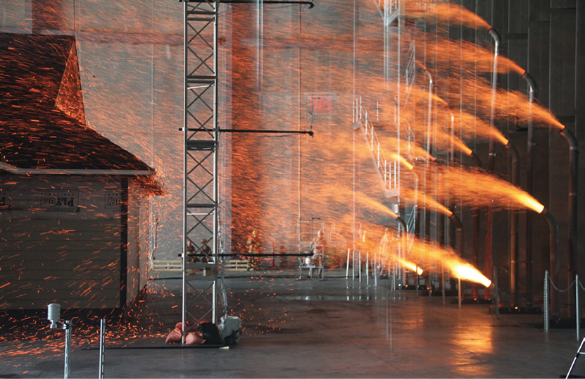 Embers are sprayed at a test home at the IBHS testing facility