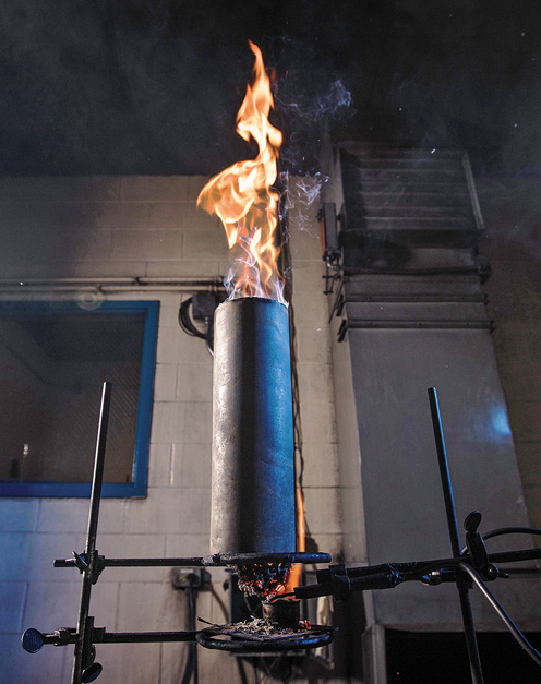 Flame jets out of a cylinder that has been filled with balled newspaper as part of a paper fire test