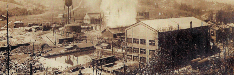 Aerial of the Aetna Chemical explosion.  Smoke rises from a building in the middle of a factory.