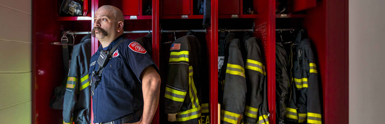 Joe Kovalsky stands next to firefighter locker while looking off camera
