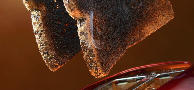 Close up of burnt toast popping out of a toaster