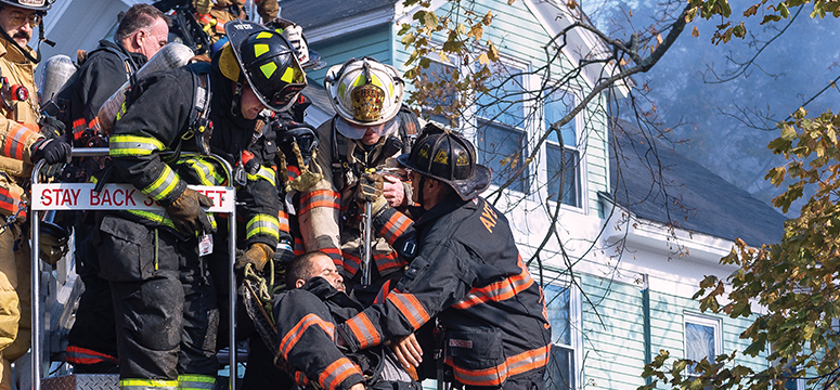 Multiple firefighters work together to bring an unconscious firefighter to safety