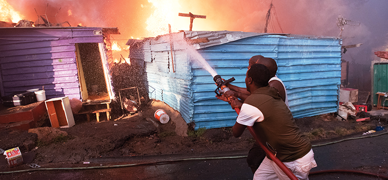 South African residents work to put out a fire in a shack