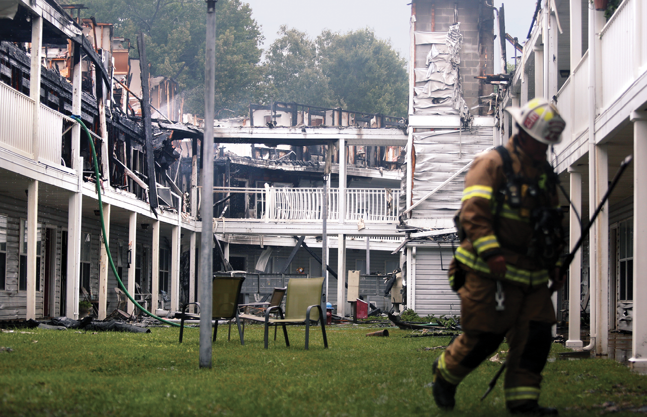 Firefighter walks away from the aftermath of a fire in a senior living complex.