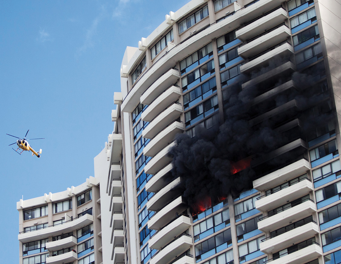 A fire department helicopter flies near a fire burning in a 36-story apartment complex in Hawaii.