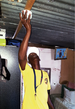 Volunteer installs a battery-powered smoke alarm in a dwelling in the Wallacedene Temporary Resettlement area