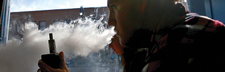 College student blows a plume of smoke from a vape