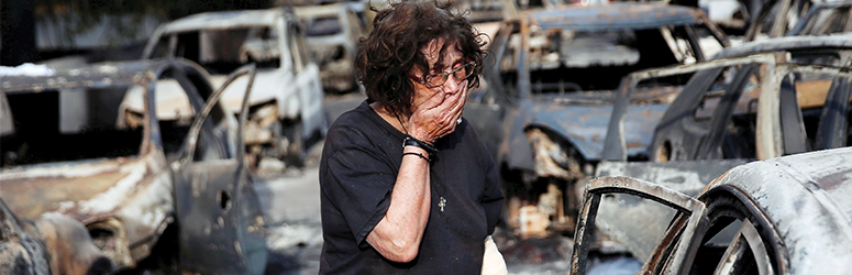 Woman in shock surrounded by burnt cars