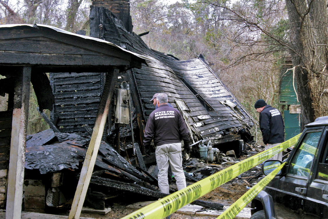Investigators examine the scorched remains of a house following a fatal fire in Mississippi