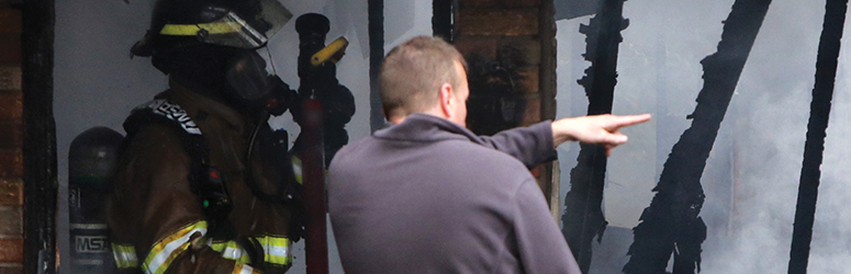 Fire Investigator pointing at the remains of a fire while a firefighter looks on