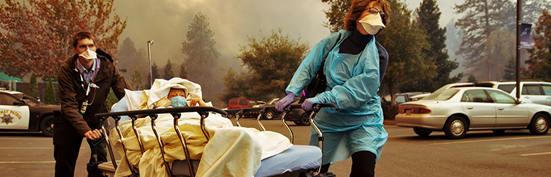 Nurses rushing a patient away in a parking lot while a smoke from a wildfire is visible in the background