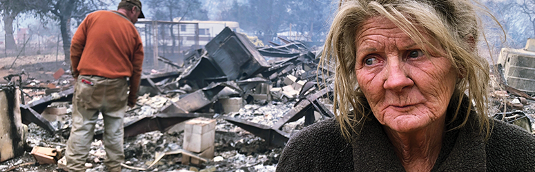 Woman looks with sadness off camera while man investigates burnt out remains of a home after a wildfire
