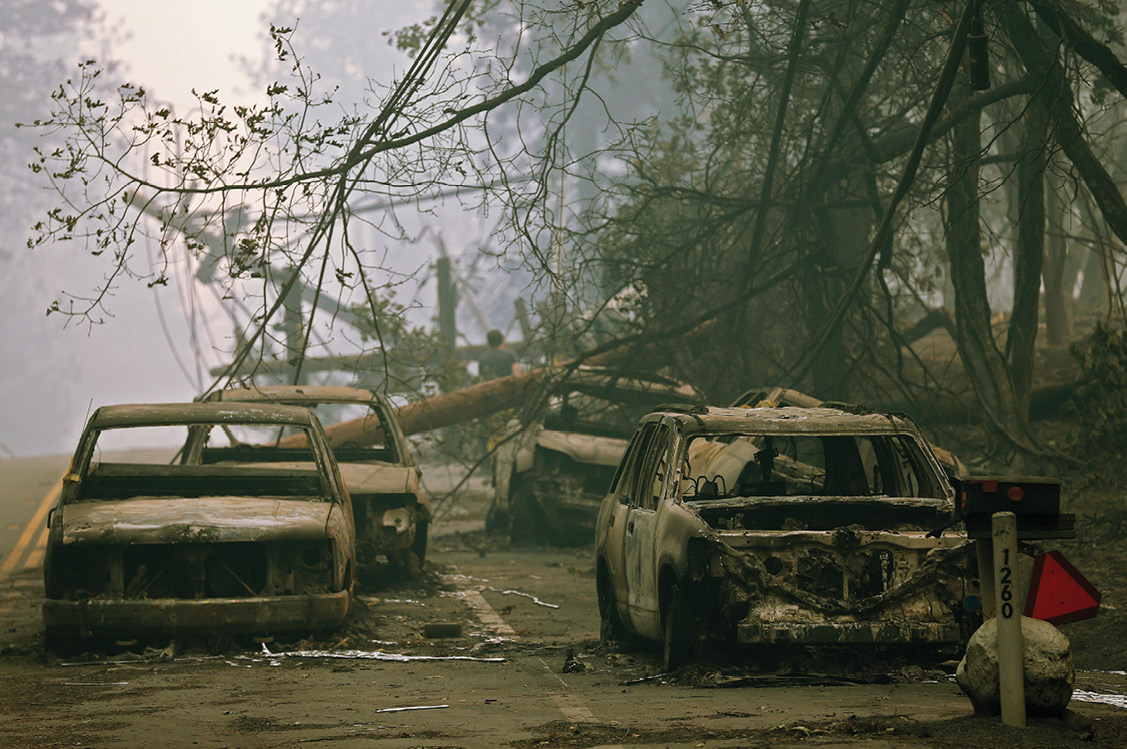 Cars are completely burnt out on a road in the aftermath of the Camp Fire