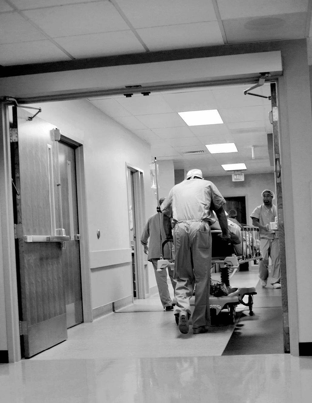 Nurses rush a patient through an egress with the doors wide open
