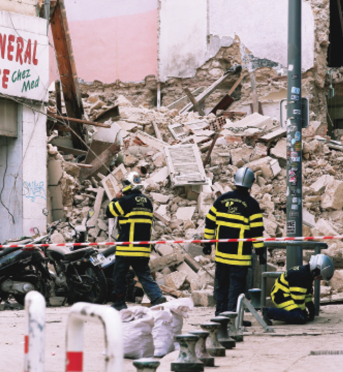 French rescue workers are seen near rubble after two deadly building collapses in central Marseille, France, in November