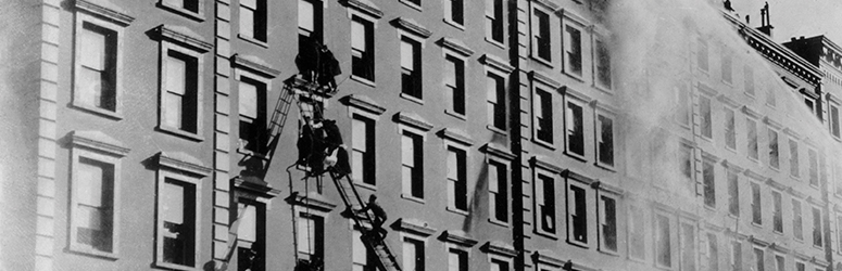 Firefighters on a ladder entering into a hotel while a fire hose sprays nearby