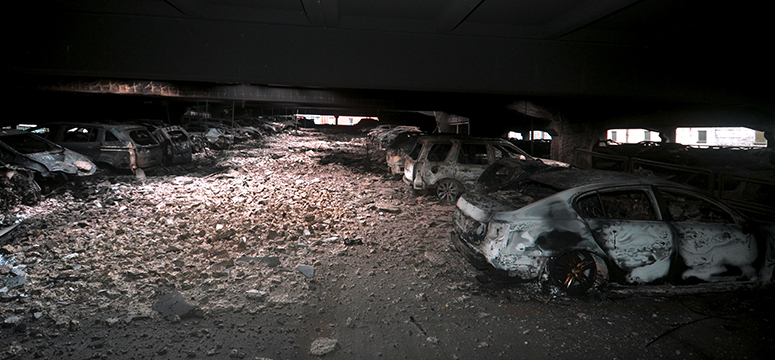 The remains of the King's Dock parking lot after the fire.  Cars sit burnt out with debris everywhere.