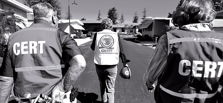 Public safety officers walk through a community with safety vest on