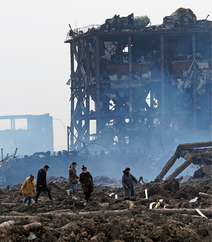 Relatives look for missing workers at the site of a pesticide plant that exploded and burned in Yancheng, China.