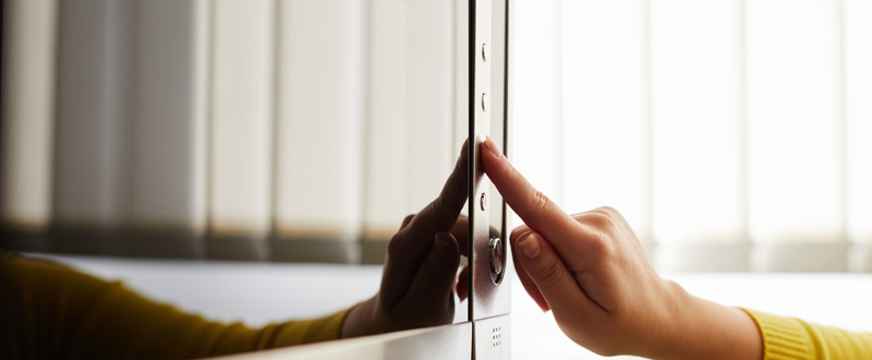 A person pushes a button on a microwave oven.
