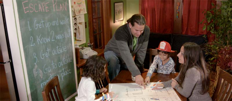 A family gathers around the table to create a home escape plan.