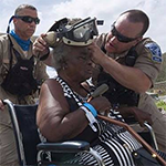 Emergency responders helping a woman in a wheelchair