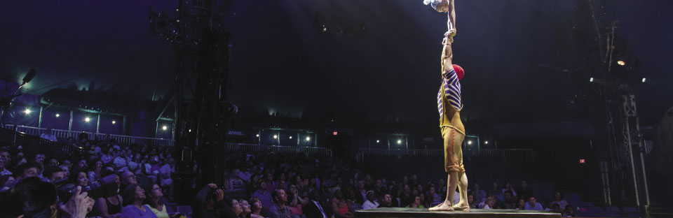 Man holding a woman vertical above his head for a Cirque de Soleil performance which an audience looks on