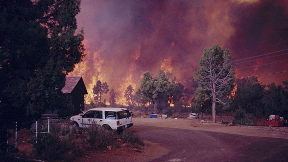 a home and automobile threatened by wildfire