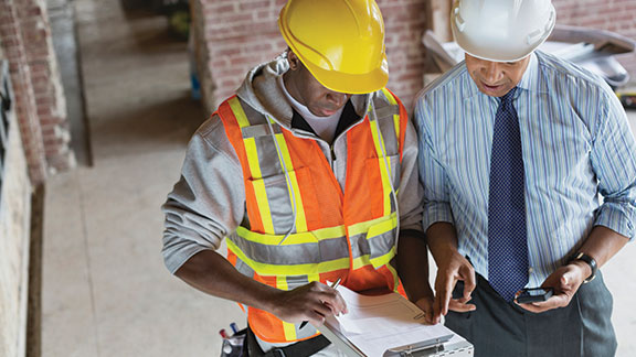 Two workers on a construction site review building plans.