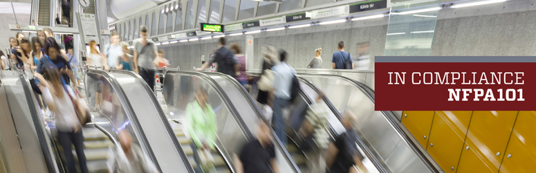 Action shot of people going up and down an escalator.
