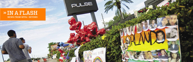Mourners walk past a memorial for victims of the Pulse Nightclub shooting
