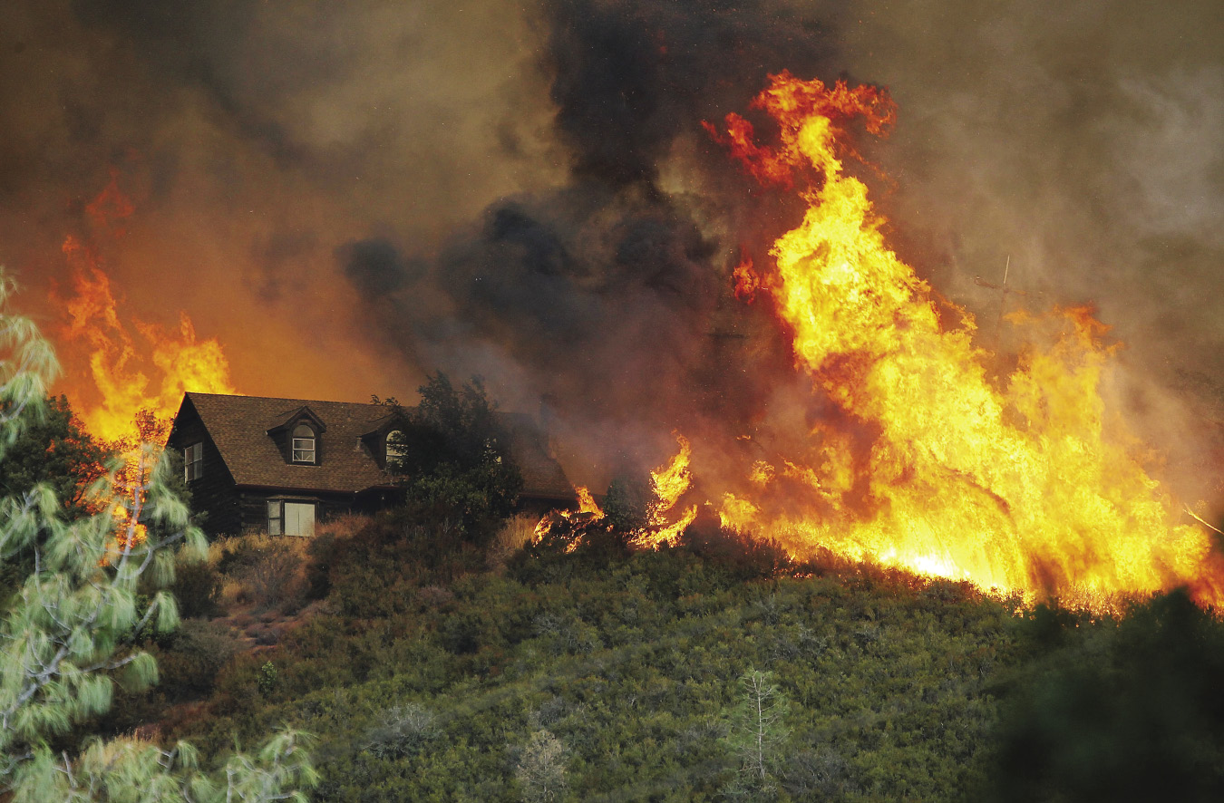 House sitting on top of hill surrounded by wildfire