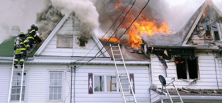 Firefighters climbing a ladder to attack a home engulfed in flames.