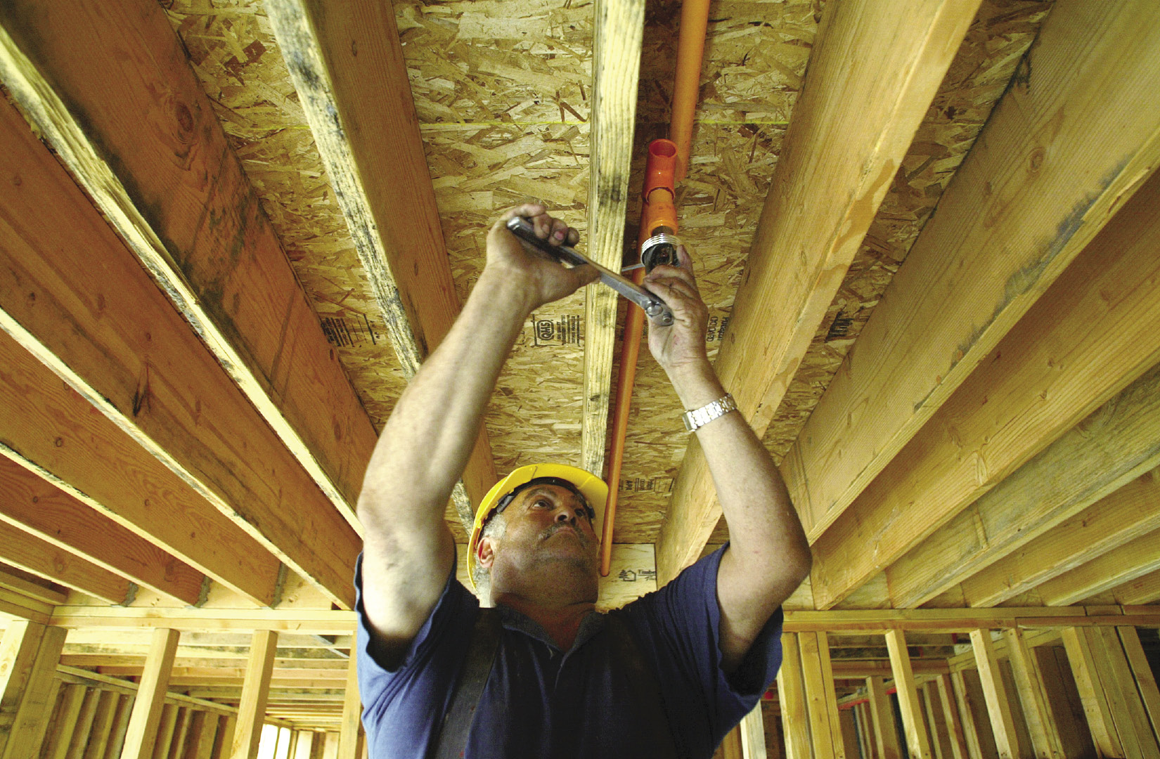 Sprinkler installer fitting a sprinkler head in a newly constructed home.