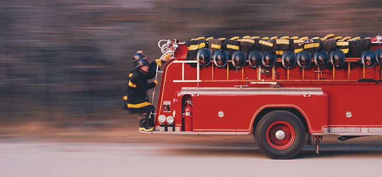 Two firefighters riding on the back of a speeding appartatus