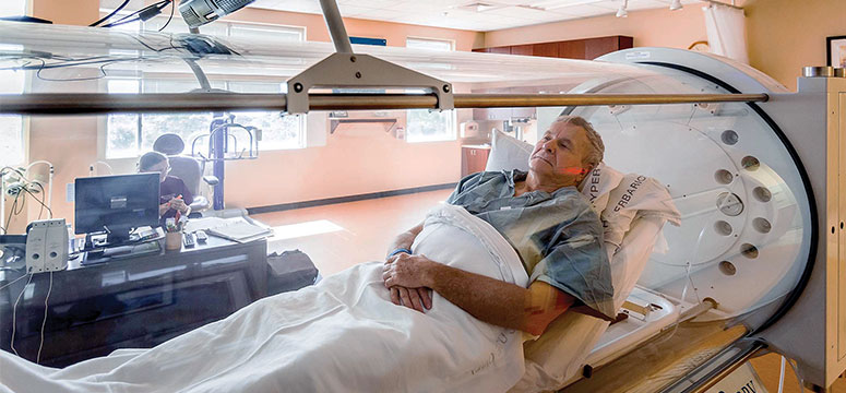 Man sits in a hyperbaric chamber
