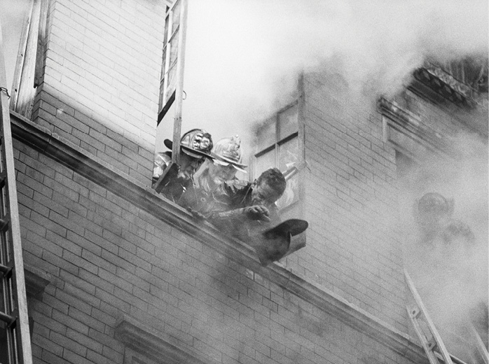 Multiple firefighters grasp for air as smoke pours out of a window they are using.