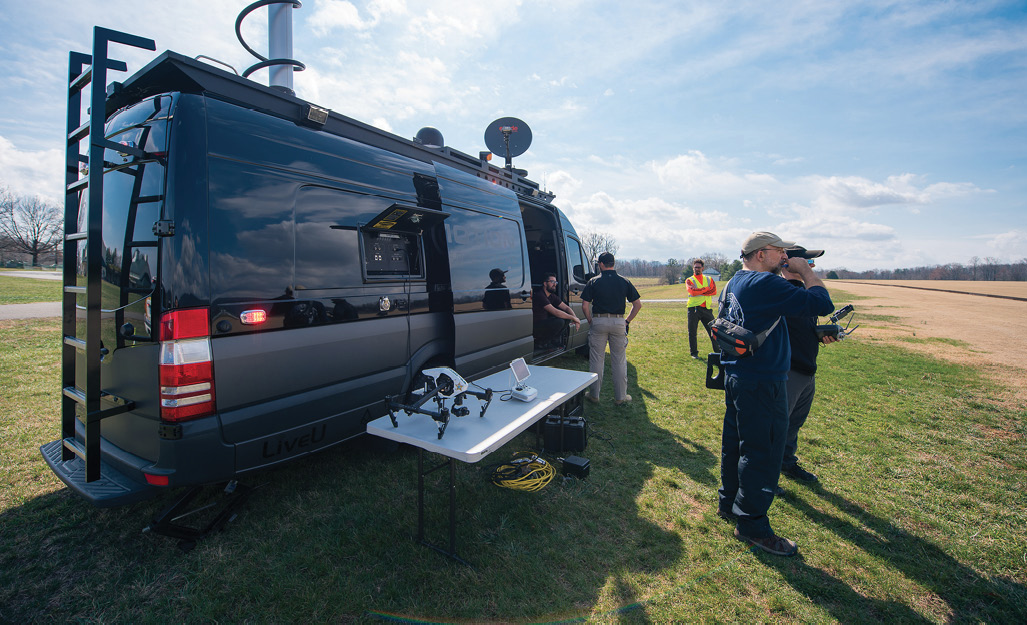 Virginia Department of Emergency Management standing next to a van with a drone displayed on a table.