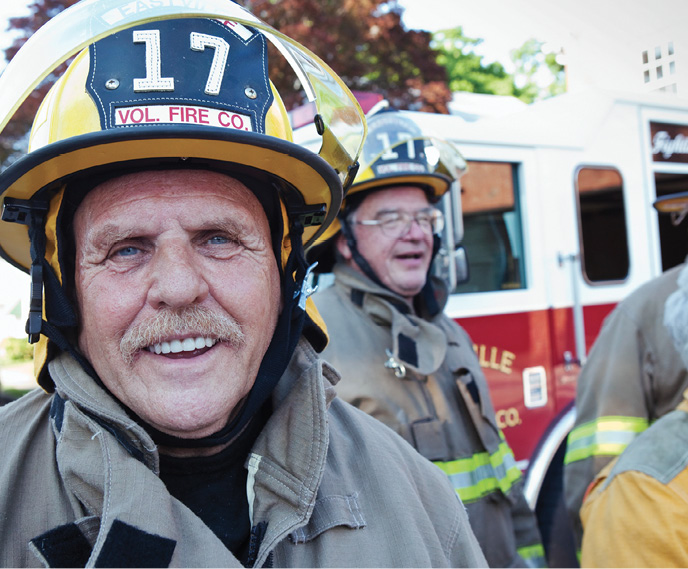 An middle aged volunteer firefighter smiles for the camera.