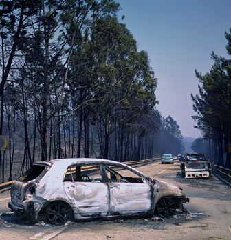 Burnt out car sits abandoned on a road with multiple burnt cars after a massive wildfire in Portugal torn through town.