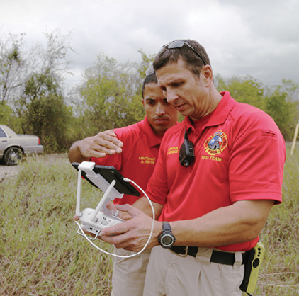 Two firefighters work with controls to pilot a drone.