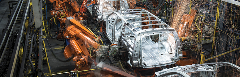 Robots work on car shell in a car manufacturing facility.