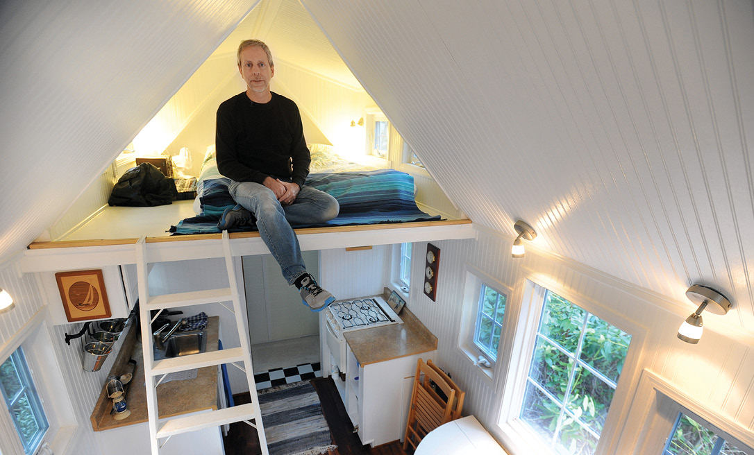 Man sits in loft of tiny house.